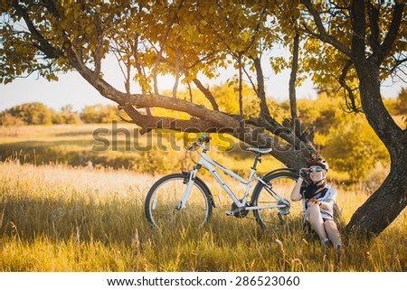 young Cyclist woman resting under a tree - stock photo