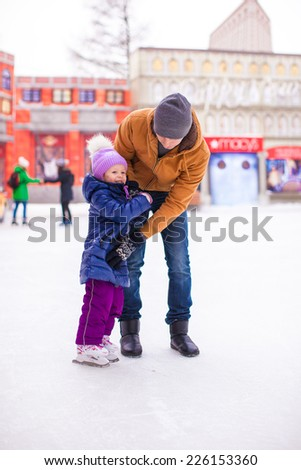 Young dad and adorable little girl have fun on skating rink - stock photo