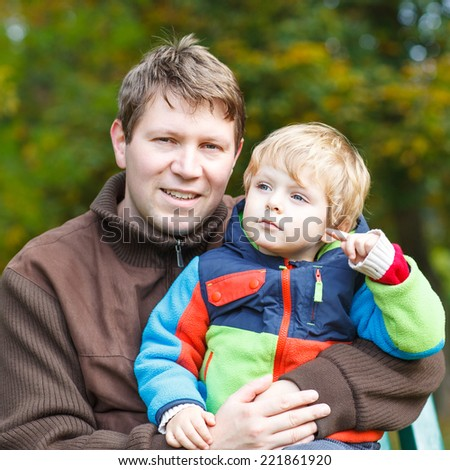 Young dad and his little toddler child in colorful clothes sitting on bench in autumn park and hugging on beautiful fall day. - stock photo