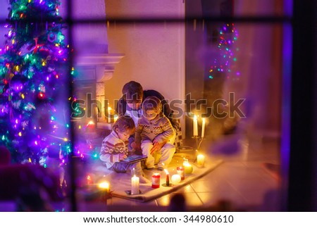 Young dad and his two little sons sitting by a fireplace at home on Christmas time. Kids boys playing with tablet. Through window from outdoors - stock photo