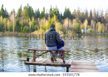 Young dad and little girl fishing on the lake - stock photo