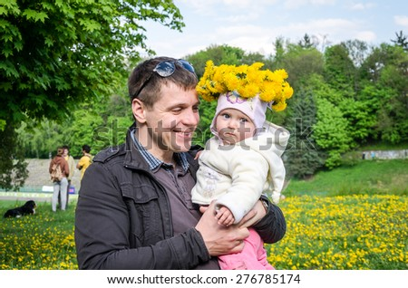 Young dad holding his little baby girl with a bouquet of flowers of dandelions on his head and smiling - stock photo