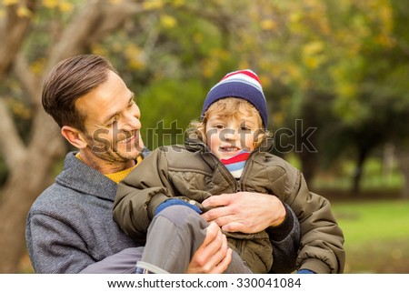 Young dad lifting his little son in park on an autumns day - stock photo