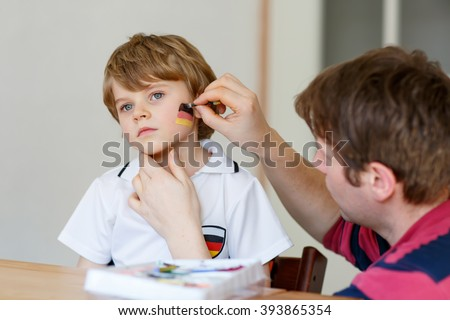 Young dad painting flag on face of little toddler son for football or soccer game. Kid boy fan happy about game of team in champions league. Selective focus - stock photo