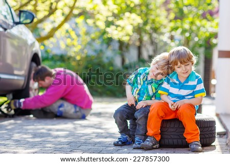 Young dad repairing car and changing wheel during his two little sibling boys sitting on big wheel, outdoors on warm sunny summer day. - stock photo