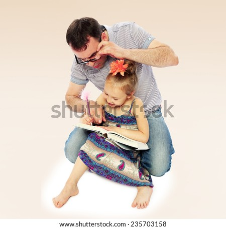 Young dad showing his young daughter how to teach the lessons of reading a book. - stock photo