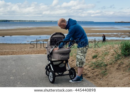 Young dad with baby stroller on beach