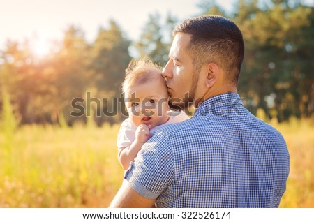 Young daddy kissing a baby. Walk autumn evening outdoors.