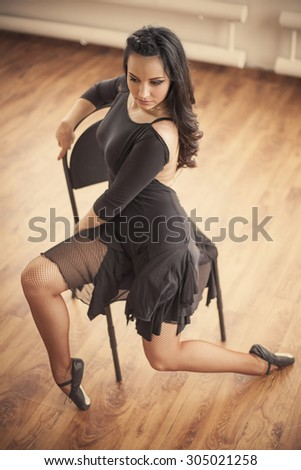 young dancer posing on chair in dance studio - stock photo