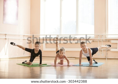 Young dancers warming up at ballet class - stock photo
