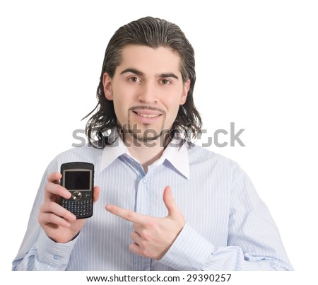 Young dark haired caucasian man in light blue striped shirt points at mobile phone and smiles isolated on white