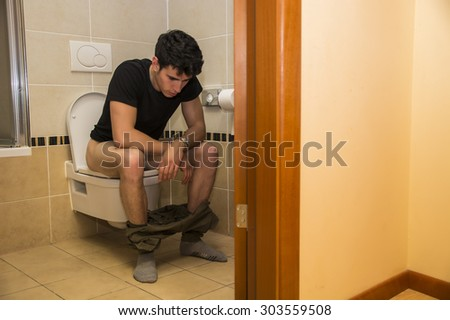 Young Dark Haired Man Sitting on Toilet with Pants Around Ankles