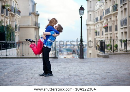 Young dating couple hugging on Montmartre, girl is jumping - stock photo