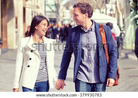 Young dating couple in love walking in city. Business people or office colleagues flirting after work holding hands on street in fall, spring or winter wearing smart casual blazer jacket and suit.