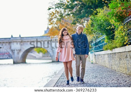 Young dating couple in Paris on a bright fall day, walking together by the Seine, colorful autumn leaves in the background