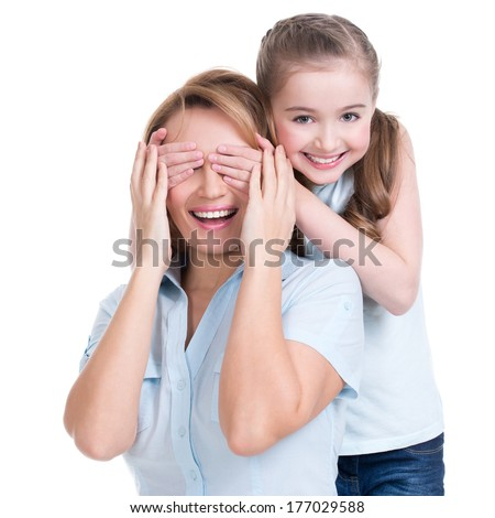 Young daughter closes hands eyes mom - isolated. Happy family people concept. - stock photo