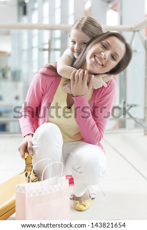 Young daughter hugs mother in shopping mall - stock photo