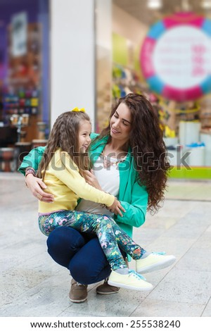 Young daughter hugs mother in shopping mall. Mother and daughter having fun in shopping mall. Emotional portrait.  - stock photo