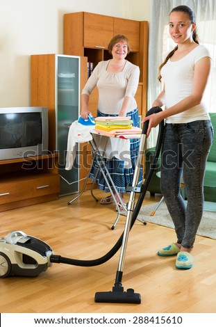Young daughter with senior mother clean at home together