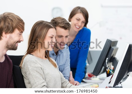 Young dedicated business team clustered around an attractive young woman seated at a desktop computer as they all peer at the monitor - stock photo