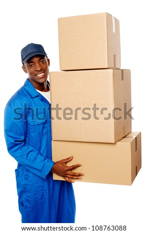 Young delivery guy holding stack of parcel boxes isolated against white