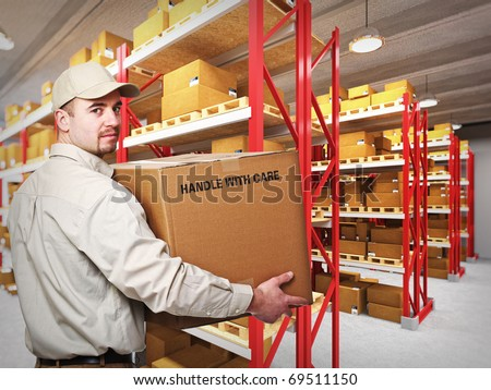 young delivery man at work in a classic warehouse - stock photo