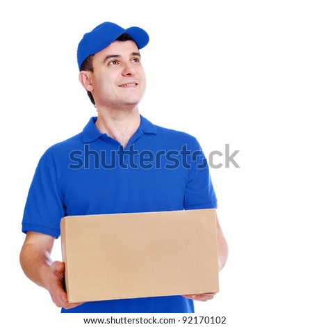 Young delivery man in blue  uniform holding the box on white background looking to the copy space area