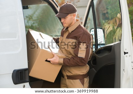 Young delivery man removing cardboard box from truck - stock photo