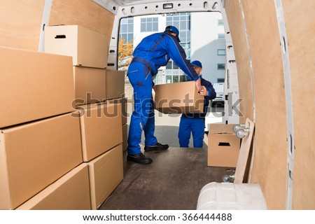 Young delivery men loading cardboard boxes in truck - stock photo