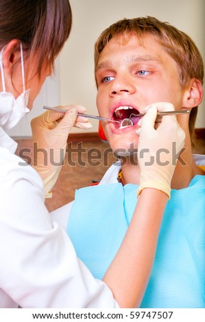 Young dentist giving a treatment to her patient - stock photo
