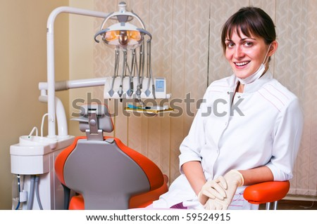 Young dentist in her office looking at the viewer - stock photo