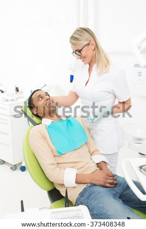 Young dentist lady smiling to her patient while man sitting in the dentist's chair and waiting for examination.