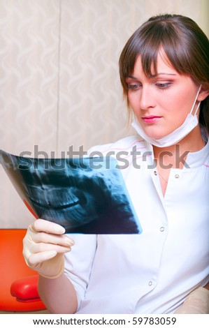 Young dentist looking at x-ray picture - stock photo