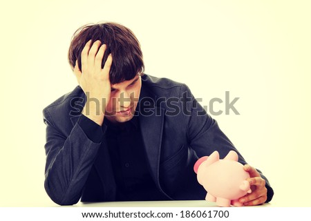 Young depressed businessman holding piggy bank. Economy crisis concept  - stock photo
