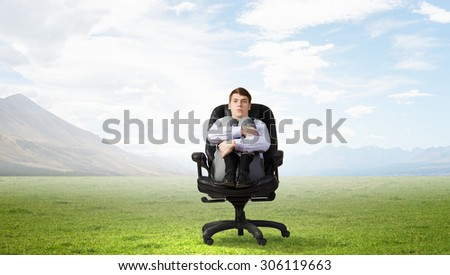 Young depressed businessman sitting in chair isolated from world