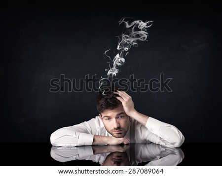 Young depressed businessman sitting with smoking head - stock photo
