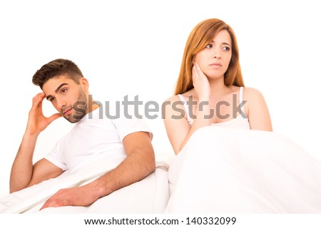 Young depressed couple in bed - daylife problems concept