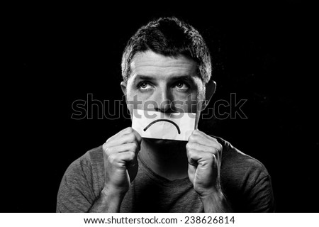 young depressed man lost in sadness and sorrow holding paper with sad mouth draw on his mouth in stress, grief, depression and lost of hope concept isolated on black background - stock photo