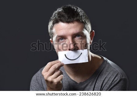 young depressed man lost in sadness and sorrow holding paper with smiley on his mouth as society forcing him to hide his pain in depression and lost of hope concept - stock photo