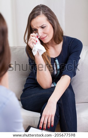 Young depressed woman crying during psychotherapy  - stock photo