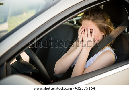 Young depressed woman holding head in hends hands sits behind steering in car
