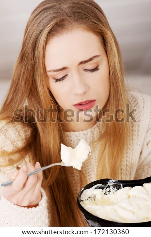 Young depressed woman is eating big bowl of ice creams to comfort herself. Depression, bulimia and diet concept. - stock photo