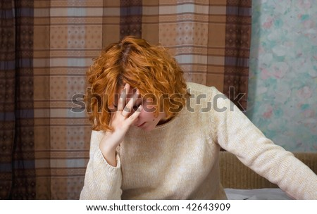 Young depressed woman sitting on the bed