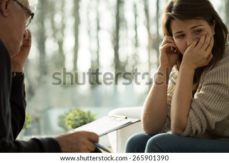 Young depressed woman taking advice from her psychologist - stock photo