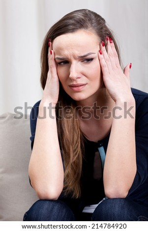 Young depressed woman with strong migraine suffering - stock photo