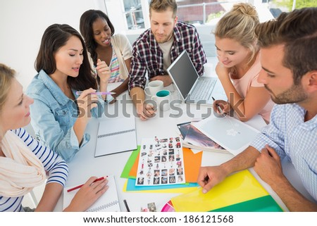 Young design team going over contact sheets at a meeting in creative office - stock photo