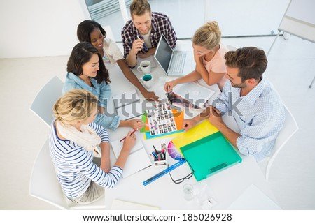 Young design team going over photography contact sheets together in creative office - stock photo