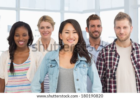 Young design team standing and smiling at camera in creative office - stock photo