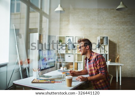 Young designer analyzing data in office - stock photo