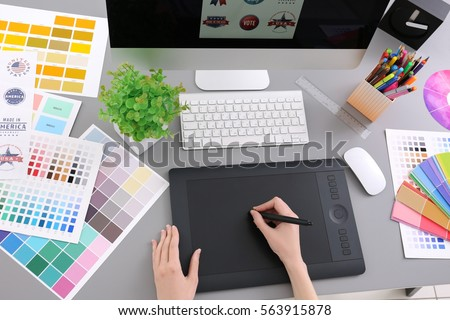 young designer drawing sketches on graphic tablet closeup - Graphic Design Desks